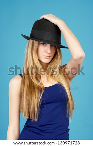 Beautiful young woman in black hat against blue background - stock photo