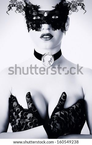 Beautiful young woman in black mysterious mask and gloves.  - stock photo