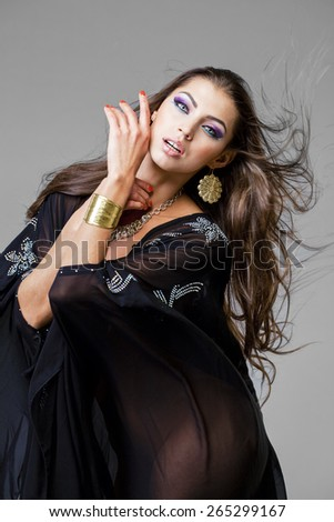 Beautiful young woman in black tunic Arabic, on gray background