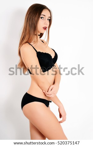Beautiful young woman in black underwear. Sexy girl in black lingerie on white background
