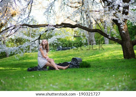 Beautiful young woman in blooming cherry garden