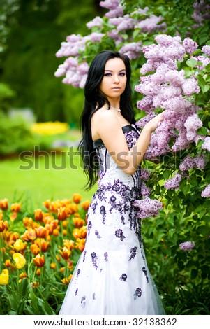 Beautiful young woman in blooming garden - stock photo