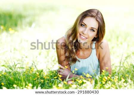 beautiful young woman in blue dress lying on grass - stock photo