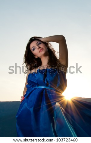 Beautiful young woman in blue dress on sunset - stock photo