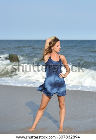 Beautiful young woman in blue dress standing on beach with waves crashing behind her  - stock photo