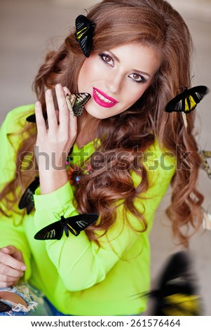 Beautiful young woman in bright clothes with exotic butterflies. Spring mood.