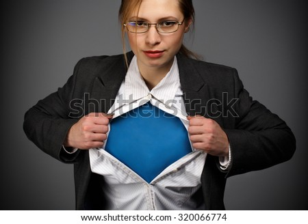 Beautiful young woman in business suit and glasses on grey background - stock photo