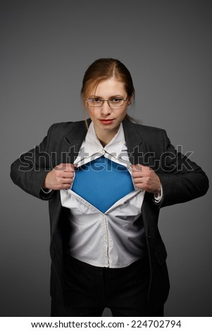 Beautiful young woman in business suit and glasses with superman concept on grey background - stock photo