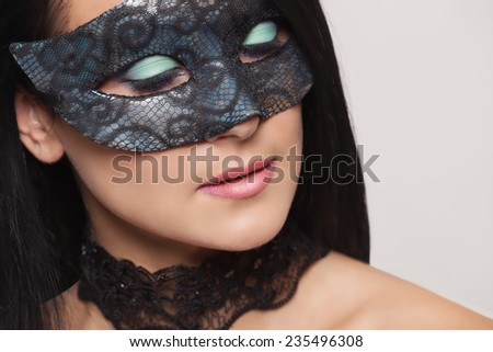 Beautiful young woman in carnival mask. - stock photo