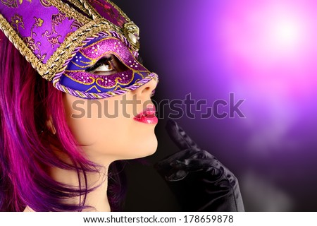 Beautiful young woman in carnival mask. Masquerade. Black background. - stock photo