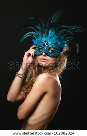Beautiful young woman in carnival mask on a black background - stock photo