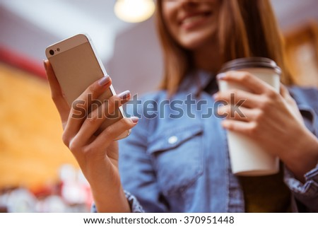 Beautiful young woman in casual clothes drinking coffee, smiling and using phone while sitting in a cafe, close-up - stock photo
