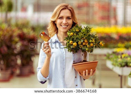 Beautiful young woman in casual clothes is looking at camera, smiling and buying plants in orangery with credit card - stock photo