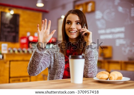 Beautiful young woman in casual clothes waving, smiling and talking on the phone while sitting in a cafe - stock photo