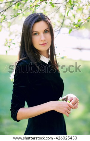 Beautiful young woman in casual wear in the flowering park - stock photo