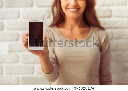 Beautiful young woman in casual wear is presenting a smartphone, looking at camera and smiling, standing against white brick wall, close up - stock photo