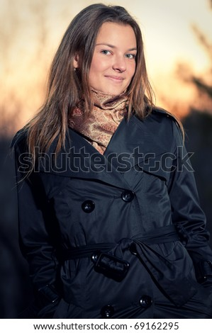 Beautiful young woman in casual wear over evening autumn nature landscape