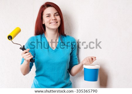 Beautiful young woman in causal clothes enjoying the result of the work she has done painting a wall. - stock photo