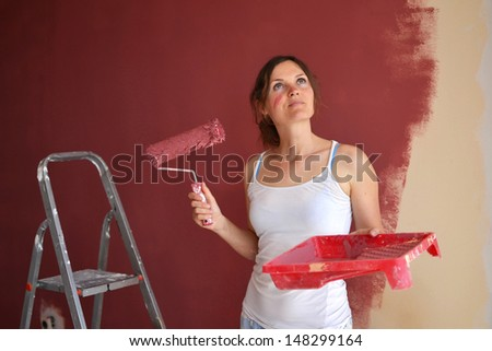 Beautiful young woman in causal clothes enjoying the result of the work she has done painting a wall - stock photo