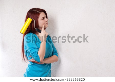 Beautiful young woman in causal clothes thinking about the result of the work she has done painting a wall with red paint and a roller. - stock photo