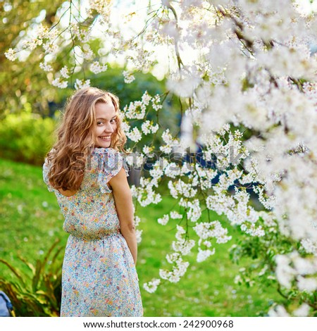 Beautiful young woman in cherry blossom garden on a spring day - stock photo