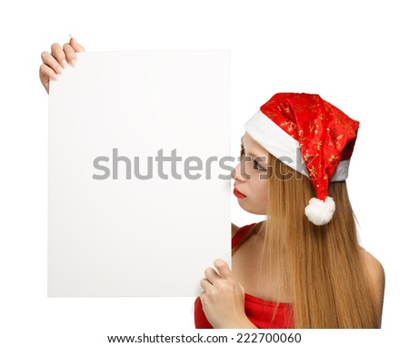 Beautiful young woman in christmas suit holding greeting card or advertisement isolated on white background