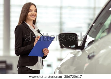 Beautiful young woman in classic suit is smiling and taking notes while examining car in a motor show