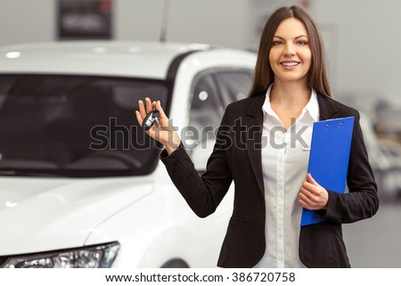 Beautiful young woman in classic suit is smiling, looking at camera and holding car keys while presenting car in a motor show - stock photo