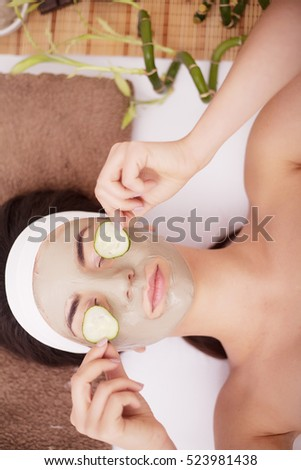 Beautiful young Woman in clay mud mask on face covering eyes with slices cucumber.