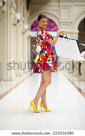 Beautiful young woman in color flowers dress walking in the shop