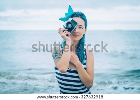 Beautiful young woman in costume of sailor takes a photograph with old photo camera on beach in summer - stock photo