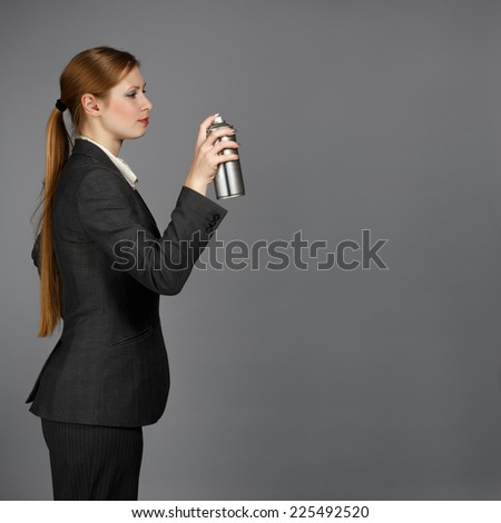 Beautiful young woman in dark business suit stands with spray can holding in hand on grey background - stock photo