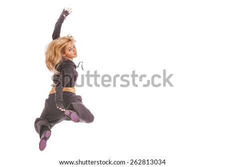 Beautiful young woman in dark dress jumping, isolated on white background. - stock photo