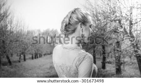 Beautiful young woman in  dress dreaming park. Posing in garden, outdoor shot. - stock photo