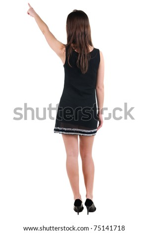 Beautiful young woman in dress pointing at wall. Rear view. Isolated over white. - stock photo