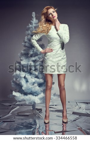 beautiful young woman in elegant dress next to christmas tree