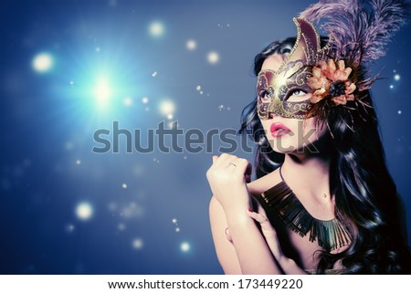 Beautiful young woman in elegant golden dress and ornate carnival mask. - stock photo