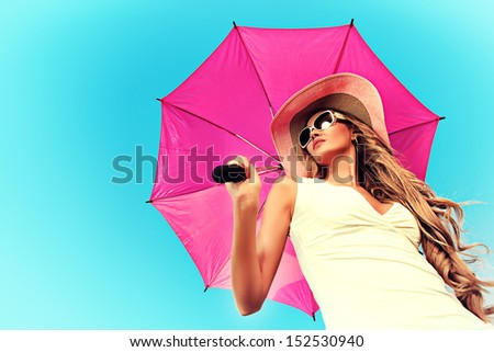 Beautiful young woman in elegant hat and sunglasses holding umbrella over sky. - stock photo