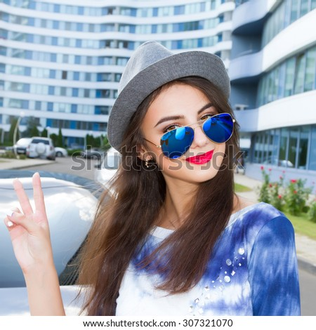 Beautiful young woman in elegant hat and sunglasses posing outdoor.Pretty young fashion smiling brunette woman in sunglasses with car posing outdoor background in spring sunny weather.Weekend.Holiday. - stock photo