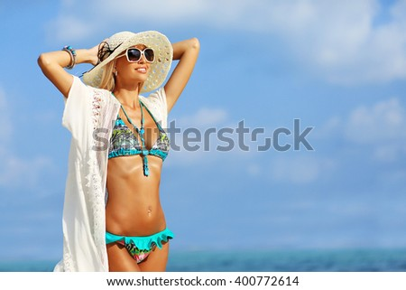 Beautiful young woman in elegant hat and sunglasses posing over the sea