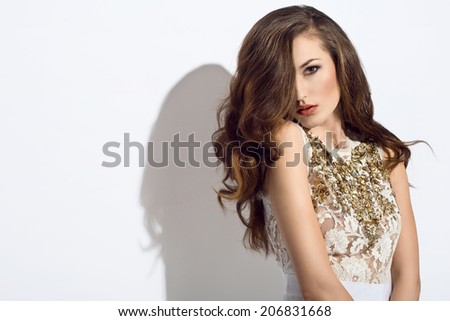 beautiful young woman in elegant white dress with golden beads and wonderful hair  - stock photo