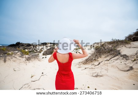 beautiful young woman in evening red dress and white hat on a background of a sand desert - stock photo