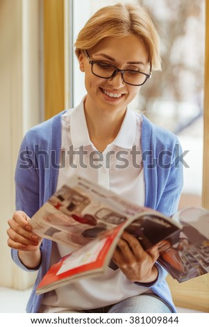 Beautiful young woman in eyeglasses reading a magazine and smiling while sitting on the window sill - stock photo
