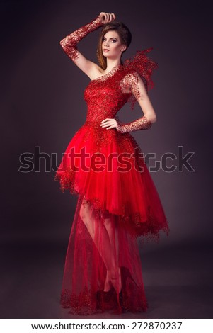 beautiful young woman in fashion red dress posing in studio