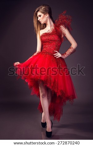 beautiful young woman in fashion red dress posing in studio - stock photo