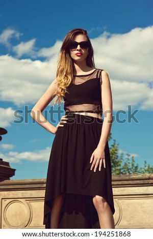 beautiful young woman in fashionable black dress. Outdoors
