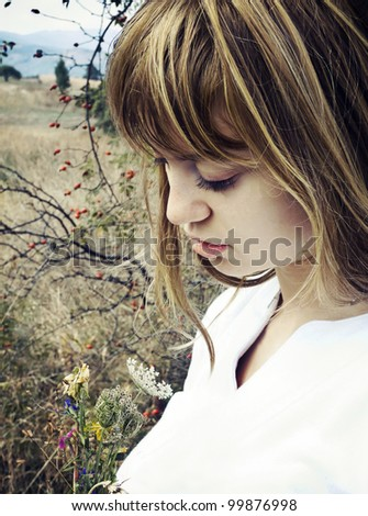 Beautiful young woman in field - stock photo