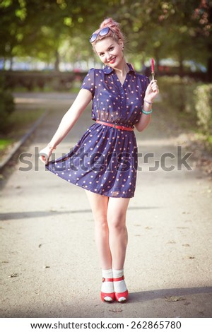 Beautiful young woman in fifties style with braces holding candy outdoor - stock photo