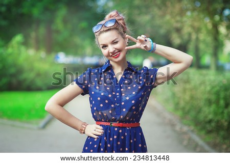 Beautiful young woman in fifties style with braces winking - stock photo