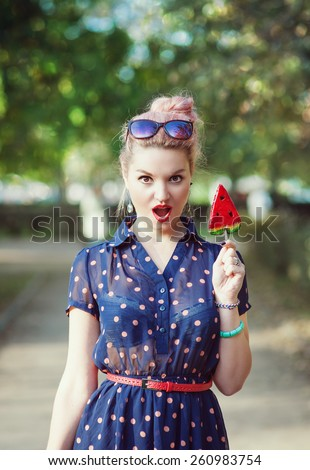 Beautiful young woman in fifties style with candy outdoor - stock photo